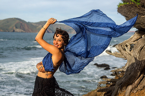 woman holding blue scarf in the wind on ocean shore, fashion, people, sea, seashore, tattoo, tree, water, windy, yassmine