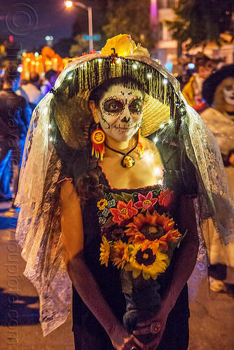 woman holding flower bouquet - dia de los muertos, bouquet, christmas lights, day of the dead, dia de los muertos, face painting, facepaint, flowers, halloween, hat, lace veil, night, sugar skull makeup, sunflowers, tassel fringe, woman