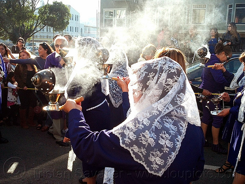 woman holding thurible with smoking incense at catholic procession, backlight, censer, crowd, incense, lace, lord of miracles, parade, peruvians, procesión, procession, religion, señor de los milagros, smoke, smoking, street, thurible, veiled, white veils, women