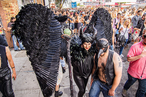 woman in black angel costume, angel costume, angel wings, bird mask, black angel, black bird, black feathers, ceremonial staff, ceremonial stick, crowd, folsom street fair, horns, man, woman