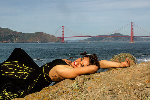 woman in black dress lying on rock near golden gate bridge, black dress, evening gowns, fashion, golden gate bridge, long dress, lying down, seashore, sunbathing, suspension bridge, woman, yassmine