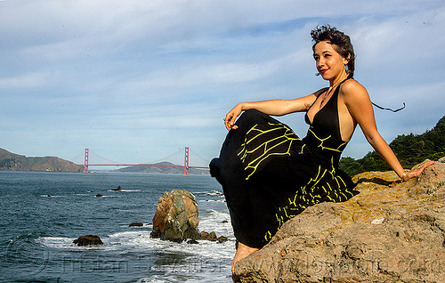 woman in black dress sitting on rock near golden gate bridge, black dress, evening gowns, fashion, golden gate bridge, long dress, ocean, sea, seashore, shore, sitting, suspension bridge, water, woman, yassmine