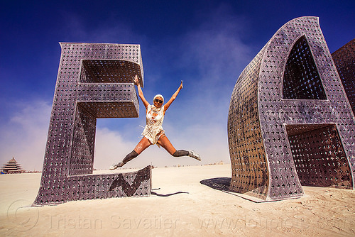 woman jumping - @ EARTH # HOME - giant letters - burning man 2016, @earth #home, art installation, big words, burning man, jump shot, metal sculpture, steel, woman