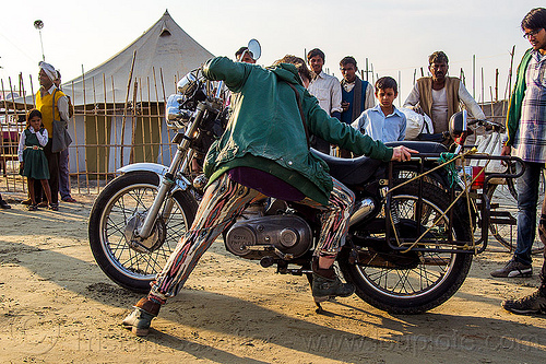 woman putting motorbike on center stand, 350cc, bun bun, hindu pilgrimage, hinduism, india, maha kumbh mela, men, motorcycle touring, motorcyclist, rider, riding, royal enfield bullet, spectators, thunderbird, watching, woman