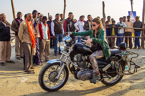 woman riding royal enfield bullet thunderbird motorcycle, 350cc, bun bun, crowd, hindu pilgrimage, hinduism, india, maha kumbh mela, men, motorcycle touring, motorcyclist, rider, riding, royal enfield bullet, spectators, standing, thunderbird, watching, woman
