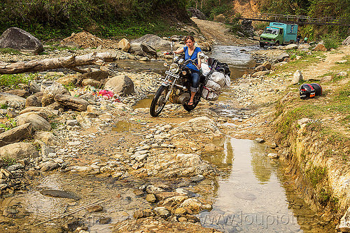 woman riding royal enfield motorcycle on dirt road (nepal), 350cc, anne-laure, bags, dirt road, fording, lorry, luggage, motorbike touring, motorcycle touring, rider, riding, river crossing, royal enfield bullet, thunderbird, truck, unpaved, water, woman