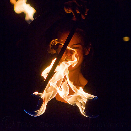 woman's face behind flames, ally, double staff, fire dancer, fire dancing, fire performer, fire spinning, fire staffs, flames, night, staves, woman