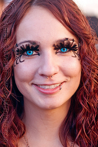 woman wiith blue color contact lenses, blue contact lenses, blue contacts, burning man decompression, color contact lenses, eyelashes extensions, feather eyelashes, lip piercing, nose piercing, redhead, septum piercing, special effects contact lenses, theatrical contact lenses, woman