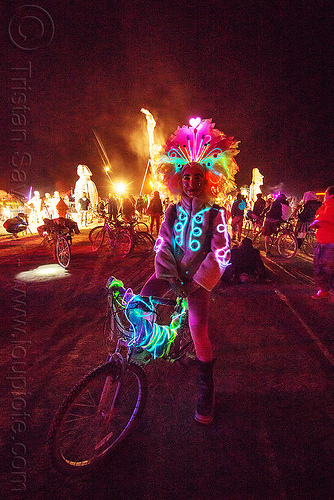 woman with glowing EL-wire costume - burning man 2015, bicycle, bike, crowd, feather headdress, feathers, japanese woman, night, people