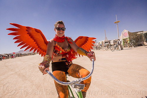 woman with orange wings - burning man 2015, bicycle, burning man, leg tattoo, orange, riding, sunglasses, woman