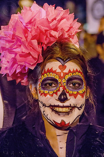 woman with sugar skull makeup and big red flower in hair - dia de los muertos (san francisco), day of the dead, dia de los muertos, face painting, facepaint, flower headdress, halloween, night, red color, sugar skull makeup, woman