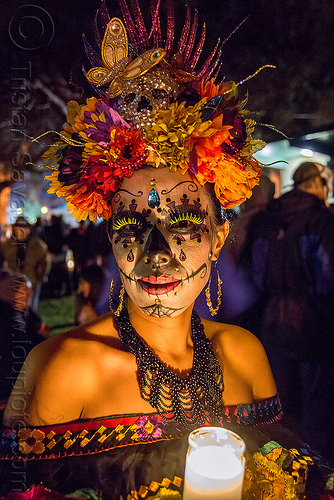 woman with sugar skull makeup and elaborate flower headdress - dia de los muertos, bindis, butterfly headdress, candle light, day of the dead, dia de los muertos, earrings, face painting, facepaint, fake eyelashes, flower headdress, glass candle, green eyelashes, halloween, necklace, night, sugar skull makeup, woman