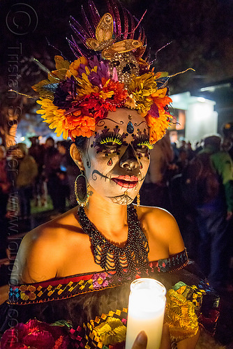 woman with sugar skull makeup and flower headdress - candle light - dia de los muertos, bindis, butterfly headdress, day of the dead, earrings, face painting, facepaint, fake eyelashes, glass candle, green eyelashes, halloween, necklace, night, people