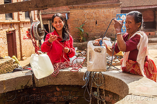 women pulling water jerrycans from water well (nepal), bhaktapur, plastic jerrycans, pulley, ropes, water well, women