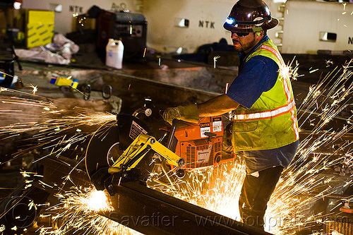 worker cutting rail with handheld abrasive  saw, 3120x, abrasive saw, cut-off saw, cutting, headlamp, headlight, high-visibility jacket, high-visibility vest, huskvama, light rail, man, muni, night, ntk, power tool, railroad construction, railroad tracks, railway tracks, reflective jacket, reflective vest, safety glasses, safety gloves, safety helmet, safety vest, san francisco municipal railway, sparks, track maintenance, track work, worker, working