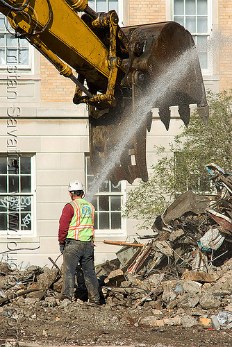 worker near excavator bucket - building demolition, abandoned building, at work, bucket attachment, caterpillar, construction worker, excavators, heavy equipment, hydraulic, machinery, man, presidio hospital, rubble, water spray, working