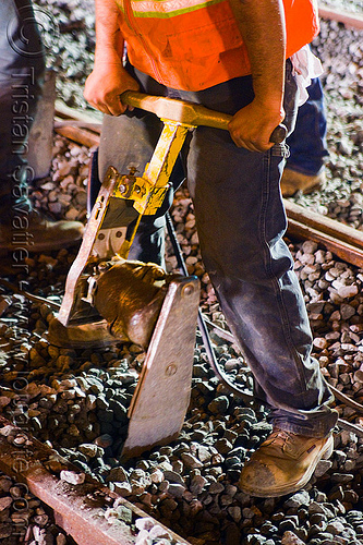 hand tamper, ballast, gravel, hand tamper, high-visibility jacket, high-visibility vest, light rail, man, muni, night, ntk, power tool, railroad construction, railroad tracks, rails, railway tracks, reflective jacket, reflective vest, safety vest, san francisco municipal railway, track maintenance, track work, worker, working