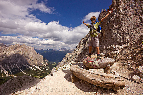 young boy at passo delle coronelle mountain pass - tschager joch - dolomites (italian alps), alps, bench, boy, dolomites, dolomiti, hiking, marker, mountaineering, mountains, sign, standing, trail, trekking