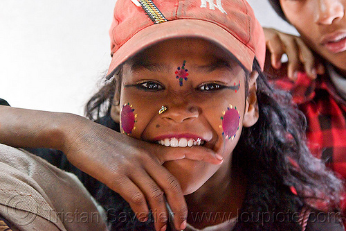 young girl biting finger (india), biting finger, cap, circus performer, contortionist, face paint, hat, india, itinerant circus, makeup, nose piercing, nostril piercing, shiny eyes, tilak