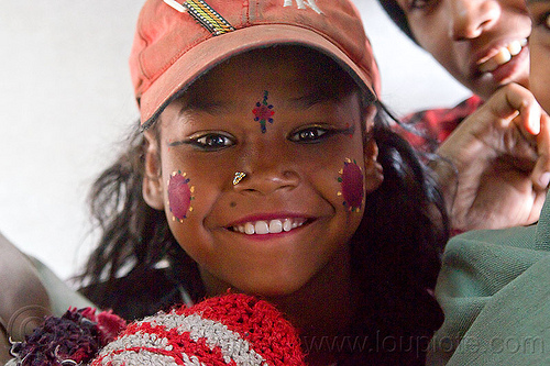 young indian girl - pierced nostril, cap, circus performer, contortionist, face paint, hat, india, itinerant circus, makeup, nose piercing, nostril piercing, shiny eyes, tilak