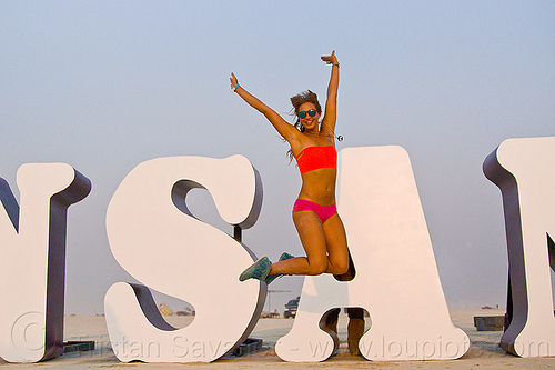 young woman jumping at INSANITY - burning man 2013, art installation, burning man, insanity, jumpshot, letters, rachel, woman