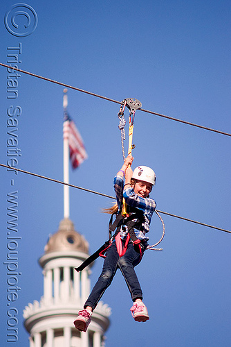 zip-line over san francisco, adventure, american flag, blue sky, cable line, cables, campanil, child, climbing helmet, clock tower, embarcadero tower, ferry building, hanging, kid, mountaineering, moving fast, speed, steel cable, trolley, tyrolienne, urban, us flag, zip line, zip wire