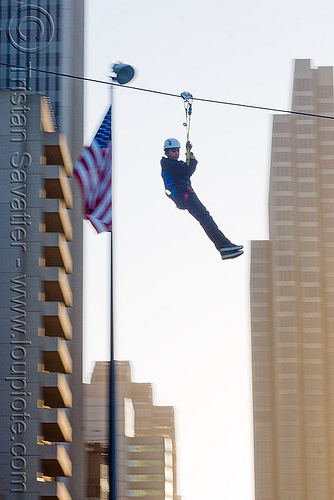 zip-line over san francisco, adventure, american flag, blue sky, buildings, cable line, cables, climbing helmet, embarcadero, extreme sport, flag pole, gear, hanging, harness, high-rise, justin herman plaza, mountaineering, moving fast, speed, steel cable, tower, trolley, tyrolienne, urban, us flag, zip line, zip wire, ziptrek
