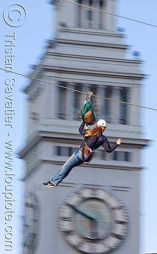 zip-line over san francisco, adventure, blue sky, cable line, cables, campanil, climbing helmet, clock tower, embarcadero tower, extreme sport, ferry building, gear, hanging, harness, justin herman plaza, mountaineering, moving fast, speed, steel cable, trolley, tyrolienne, urban, woman, zip line, zip wire, ziptrek