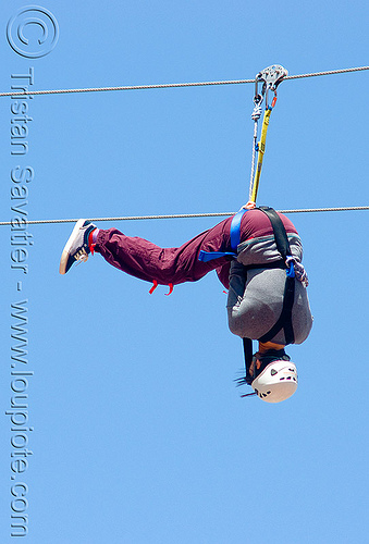 zoey riding the zip-line over san francisco, adventure, blue sky, cable line, cables, climbing helmet, embarcadero, hanging, mountaineering, moving fast, speed, steel cable, trolley, tyrolienne, upside-down, urban, woman, zip line, zip wire