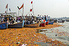 boats and flower offerings on the ganges river, flags, floating, ganga river, ganges river, hindu, hinduism, kumbha mela, maha kumbh mela, offerings, orange flowers, paush purnima, pilgrims, river boats, triveni sangam, water, yatris