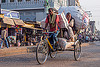 man riding with large sacks of freight on cycle rickshaw (india), bags, cargo, cycle rickshaw, freight, load, men, moving, riding, sacks, street, transport, transportation, transporting, varanasi
