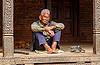 old nepali man sitting in a pati (nepal), bare feet, bhaktapur, hat, old man, pati, pillars, prescription glasses, shoes, sitting, spectacles, walking cane, walking stick, wood carving, wooden