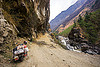 motorbike on road between tatopani and jomsom (nepal), annapurnas, bags, cliff, dirt road, kali gandaki river, kali gandaki valley, luggage, motorbike touring, motorcycle touring, mountain road, mountains, sacks, stream, unpaved, water