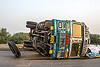 overturned truck on highway median (india), cargo, crash, freight, load, lorry, overturned, rice bags, road, rollover, spilled, tata motors, traffic accident, truck accident, wheels, wreck
