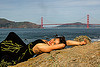 woman in black dress lying on rock near golden gate bridge, black dress, evening gowns, fashion, golden gate bridge, long dress, lying down, ocean, sea, seashore, shore, sunbathing, suspension bridge, water, woman, yassmine
