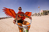 woman with orange wings - burning man 2015, bicycle, burning man, leg tattoo, orange, riding, sunglasses, wings, woman