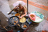 old woman cooking excellent little cakes in the market - luang prabang (laos)