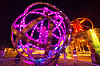 woman inside giant animated steel rings sculpture - burning man 2016, animated, art installation, burning man, disc-go-sphere, glowing, led light, metal, night, sculpture, the man, woman