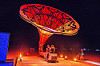 couple sitting under la victrola - giant gramophone - burning man 2016, art installation, burning man, giant gramophone, la victrola, night
