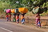 women in sari carrying bags on their head (india)
