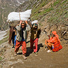 porters carrying heavy loads on trail - sadhu resting on trail - amarnath yatra (pilgrimage) - kashmir