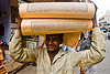 boy with load of printed paper (india)