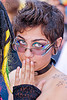 hand on mouth, bindis, emma, eye makeup, eyeglasses, eyewear, gay pride festival, gouged ears, green eyed, green eyes, nose ring, prescription glasses, shoulder tattoo, spectacles, stars tattoo, woman