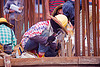 construction worker building concrete formwork, building construction, concrete forms, concrete wall forms, construction site, construction workers, face mask, formwork, hammer, lumber, man, miri, rebars, safety helmet, squating, straw hat, sun hat, timber, working