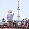 construction surveying - theodolite and tower ruler, building construction, construction site, construction surveying, construction surveyor, construction workers, geometer, islam, man, minaret, miri, mosque, safety helmet, standing, straw hat, sun hat, survey, theodolite, thumb up, tower ruler, tripod