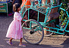 little girl with pink dress near a rickshaw