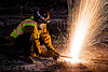 welder cutting a train rail with an oxy-acetylene torch, demolition, high-visibility jacket, high-visibility vest, light rail, man, muni, night, ntk, oxy-acetylene cutting torch, oxy-fuel cutting, railroad construction, railroad tracks, rails, railway tracks, reflective jacket, reflective vest, safety helmet, safety vest, san francisco municipal railway, sparks, track maintenance, track work, welder, welding, worker, working