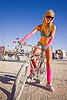 pink leg warmers - burning man 2012, bicycle, blonde, burning man, fashion, neon colors, standing, sunglasses, woman