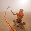 mini kite, boots, burning man, dust storm, flying, goggles, haboob, minah, mini kite, orange scarf, playa dust, red, sitting, streamers, string, whiteout, wind, woman, yellow