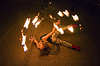 fire dancer laying on the ground with fire fans - cressie mae